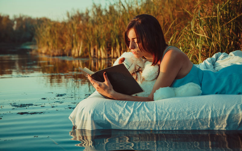 Harper Lee Umberto Eco woman reading book on floating mattress with teddy bear
