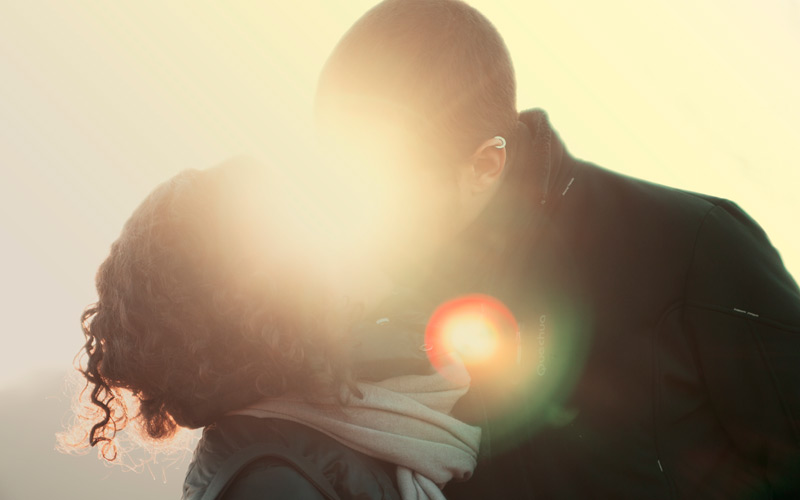 a man and woman kissing in silhouette