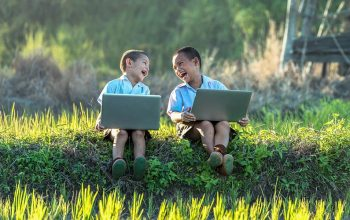 kids laughing together at their laptops