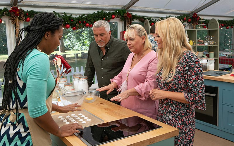 Great American Baking Show contestant Destane with returning judge Paul Hollywood, plus new judge Sherry Yard and new co-host Emma Bunton