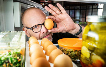 Alton Brown poses with an egg for Good Eats: The Return