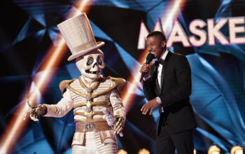 The Masked Singer season 2 contestant known as Skeleton with host Nick Cannon on the season premiere.