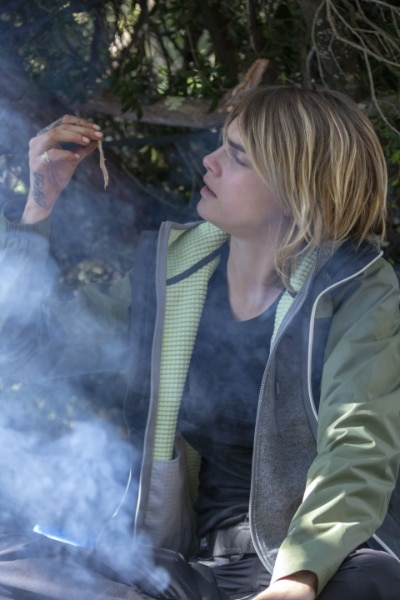Cara Delevingne looks at a cooked rat during her episode of Running Wild with Bear Grylls