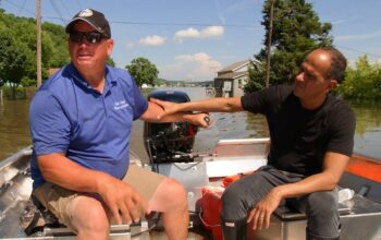 Grafton, Ill., mayor Rick Eberlin and The Profit star Marcus Lemonis surveying the flooded parts of the town.