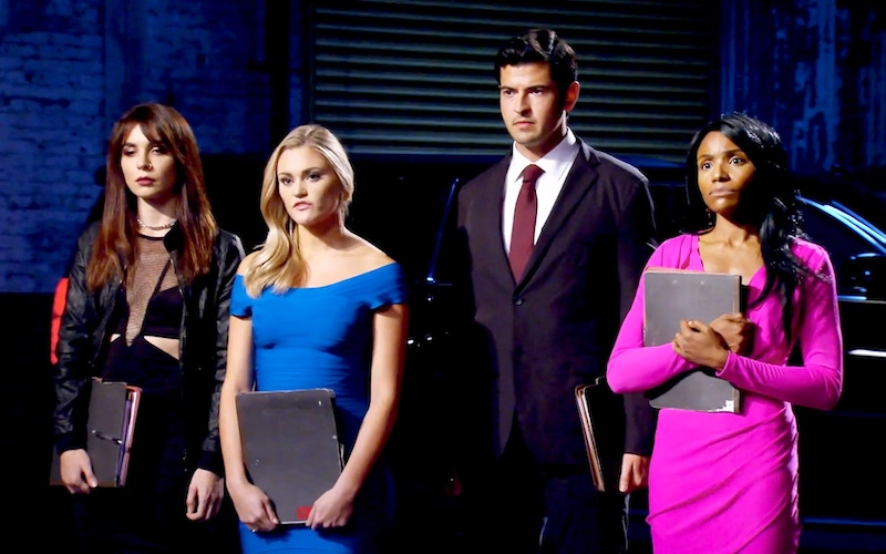 Four contestants on Bravo's Spy Games—Jessica Studnickey, Chelsea Mori, George Jackson, and Charnel Wright—hold their dossiers and face assessment