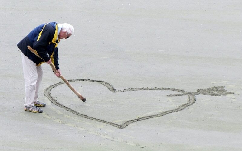 An older man draws a heart in sand