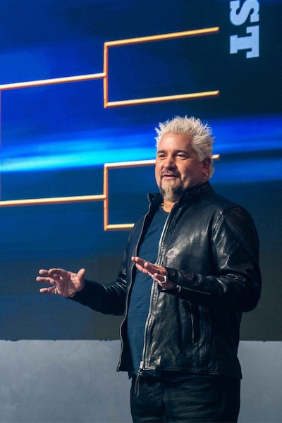 Tournament of Champions host Guy Fieri in front of the show's bracket