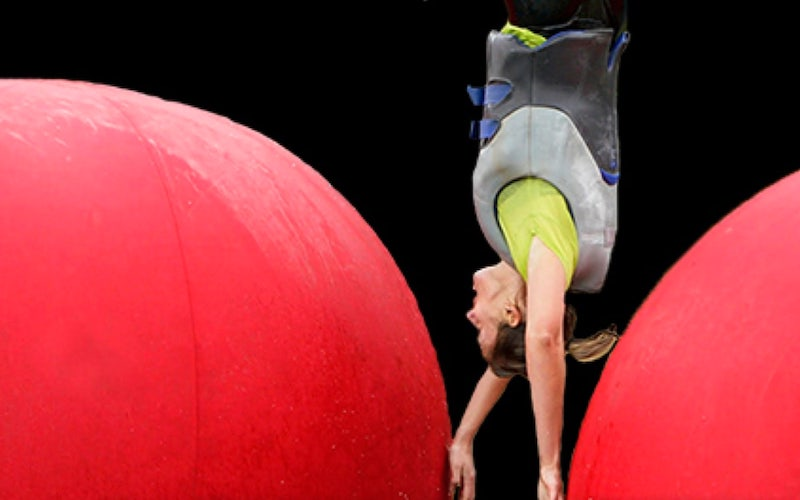 A contestant flips between two of Wipeout's iconic big red balls on a casting flyer for TBS's revival of the reality show