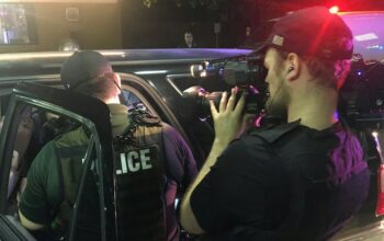 A photo from Cops season 30 that the show posted to social media, showing a camera operator filming an officer searching a car