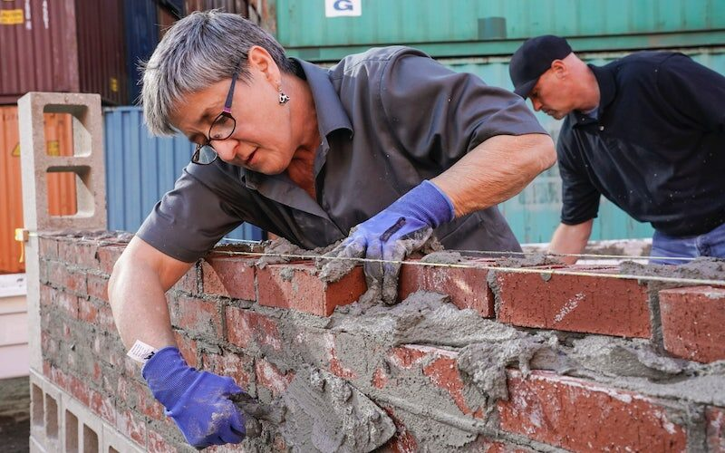Michelle S. Kiddy competes in Tough As Nails' second challenge, which asked the contestants to lay bricks