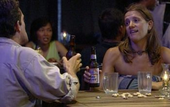 Jeff Probst and Kelly Wiglesworth drinking Bud Light in a fake bar constructed at Survivor's base camp and populated by crew members