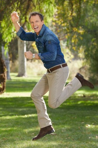 Phil Keoghan, photographed jumping in the air with excitement over The Amazing Race 32