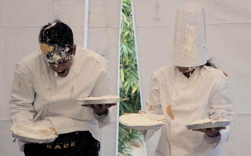 Eswar Dhinakaran and Aparna Dhinakaran getting hit with chantilly cream pies on The Amazing Race 32