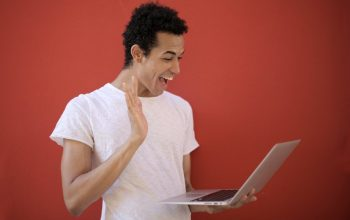 A stock photo of a person looking at a laptop in surprise, like I did when I saw CBS.com's Survivor cast pages