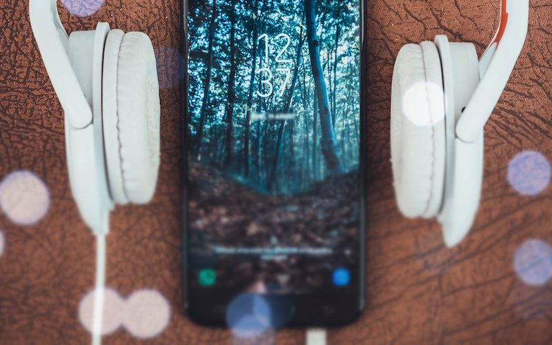 Relaxing podcasts: headphones surrounding a phone with a relaxing forest scene