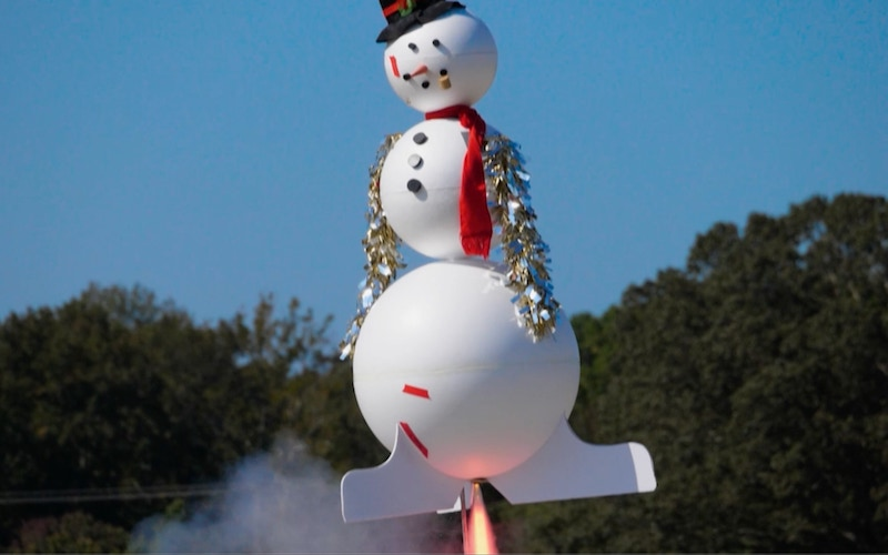 A snowman-themed rocket blasts off on Discovery Channel's Rocket Around the Xmas Tree
