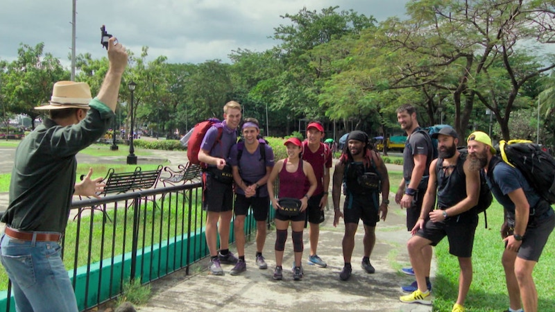 Phil Keoghan fires a starter pistol to start The Amazing Race 32's final four teams—hil Keoghan, Will Jardell, James Wallington, Hung Nguyen, Chee Lee, DeAngelo Williams, Gary Barnidge, Riley McKibbin, and Maddison McKibbin—on the city spring in Manila