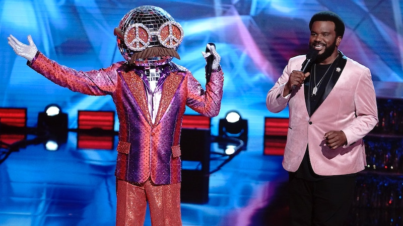 Masked Dancer host Craig Robinson, right, with the contestant known as Disco Ball