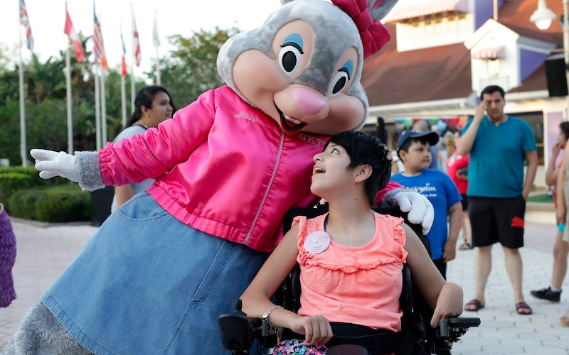 A costumed bunny character, Merry, hugs Gabriella, a visitor to the Give Kids the World Village in Orlando, Fla.