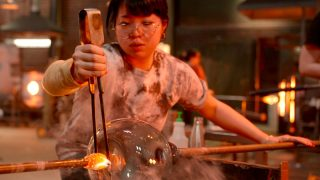 Nao Yamamoto, a contestant on Blown Away season 2, works on piece in the hot shop