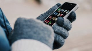 Someone wearing mittens uses a phone in the cold.
