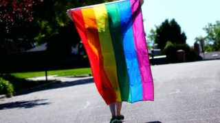 A person holding up a pride flag—an image you will not currently find on the streaming service CuriosityStream