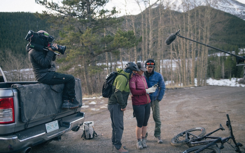 Team North America looks at their route while a camera crew films them on Race to the Center of the Earth (Team North America checks Garmin to find their next way point