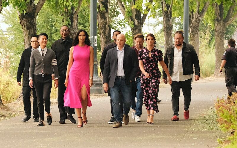 Top Chef Portland's judges walking through a park in episode 1. From left to right: Dale Talde, Melissa King, Gregory Gourdet, Padma Lakshmi, Kwame Onwuachi, Tom Colicchio, Richard Blais, Gail Simmons, and Amar Santana