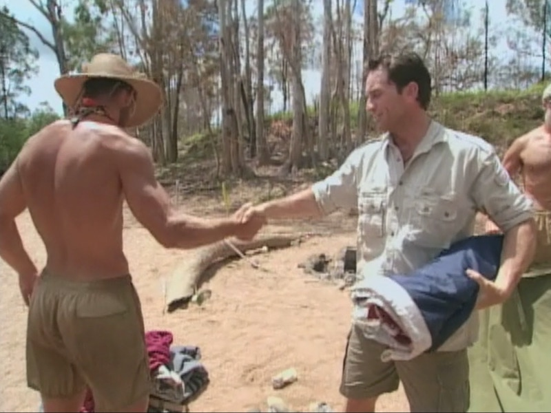 Colby Donaldson shakes Jeff Probst's hand after handing over his luxury item, the Texas flag, which was being used as a roof for their shelter.
