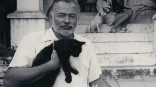 Ernest Hemingway with a cat at his home in Cuba