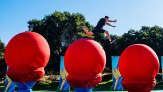 A contestant navigates the big red balls on Wipeout's new course