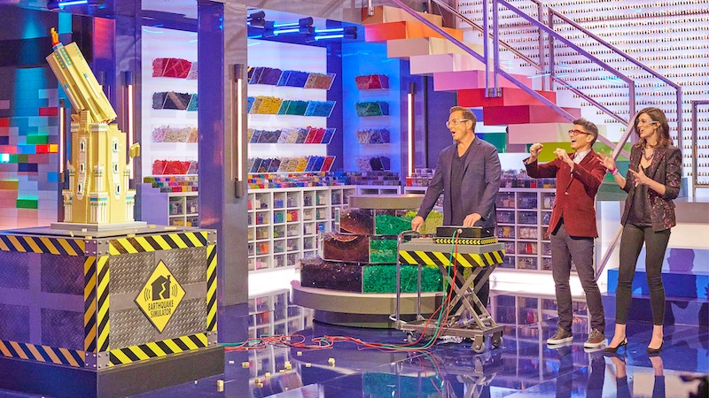 Lego Masters host Will Arnett tries to make a build collapse in a simulated earthquake as judges Jamie Berard and Amy Corbett watch