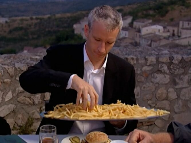 Anderson Cooper grabs McDonald's french fries during the players' Mickey D's dinner on The Mole 2: The Next Betrayal episode 11