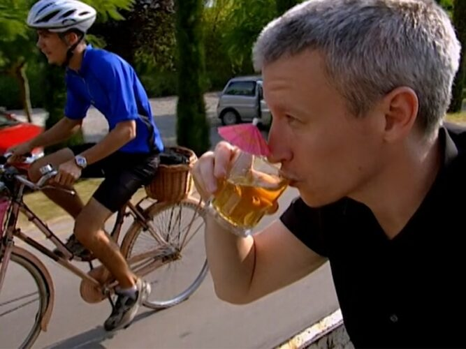 Anderson Cooper sips a cocktail while Bribs peddles uphill on The Mole 2, episode 6.